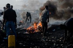 電化製品を燃やし中の金属を取り出す焼き場の若者