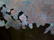 The corroded surface of an old, rusty oil barrel