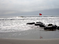 Red flagged stone breaker along the shore