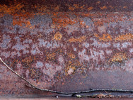The rusty surface of a corroded steel I-beam