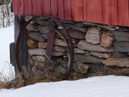 An old barn with a stone wall foundation and metal hoops, in winter
