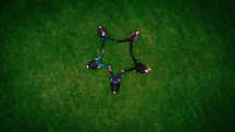 People Lying on Grass Forming a Star Sha