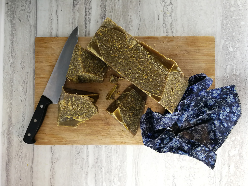 chunks of cut beeswax displayed on a cuttingboard.