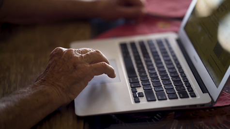 a hand hovers over a laptop keyboard