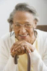 smiling woman leans on her cane while sitting in her living room