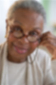 senior lady with glasses faces the camera
