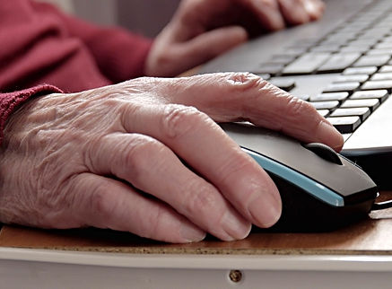 elderly hand using mouse with computer