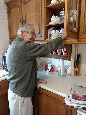 happy senior reaches into kitchen cabinet