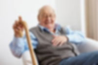 senior gentleman using a cane relaxes at home