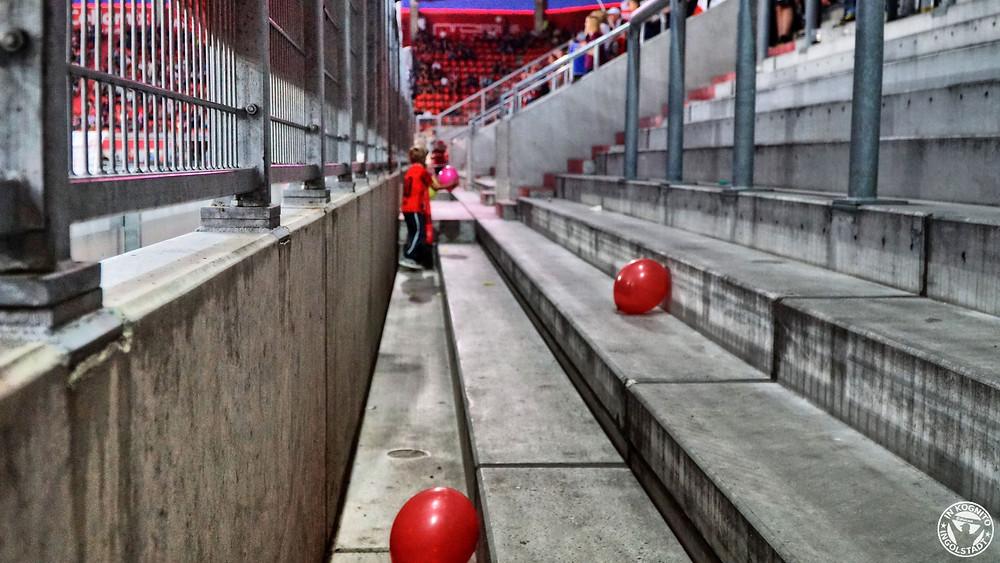 rote Luftballons auf den leeren Stufen der Südtribüne