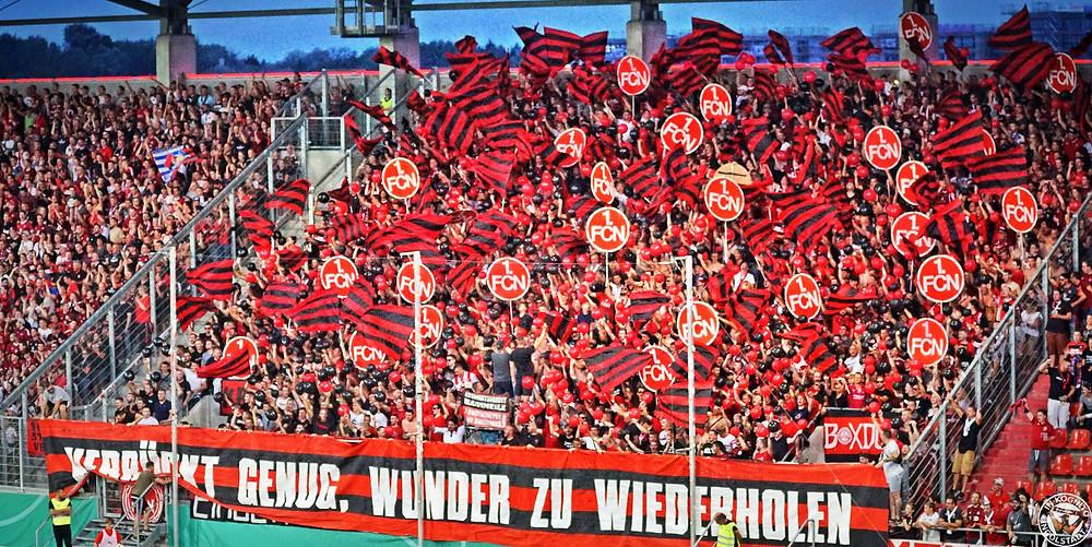 """Blick auf die Gästekurve mit Nürnberg Fans. Sie zeigen eine Choreographie aus schwarz-roten Fähnchen und """"1. FCN"""" Schildern"""