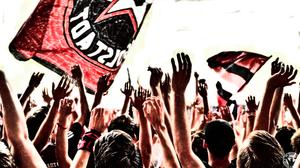 """Menschen auf der Südtribüne reißen die Arme hoch. Es wurde von hinten fotografiert, vorne sieht man die Fahne der """"Supporters Ingolstadt"""""""