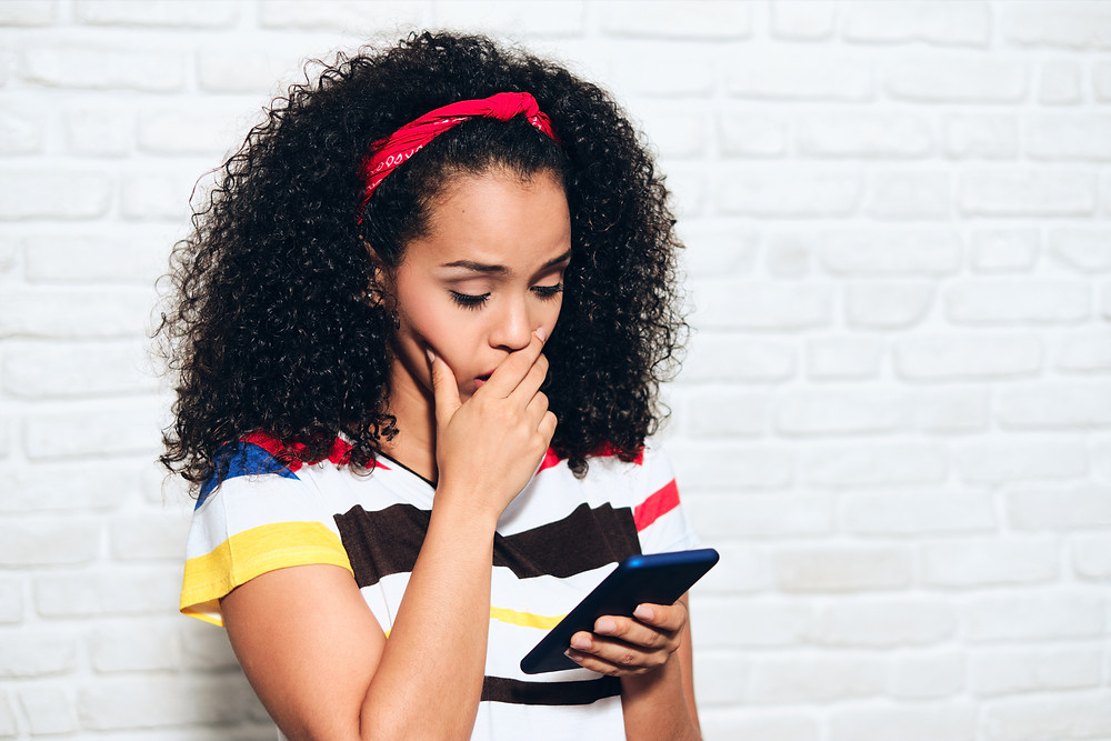 Girl concerned by what she reads on her smart phone