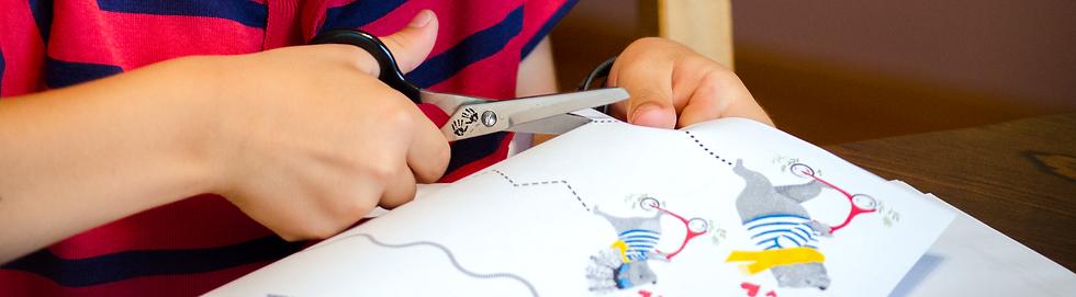 child using no-slip grip scissors to practice scissor skills on free printable acttivity sheet