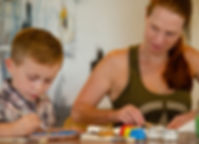 mom and son electronic-free time painting all natural air-dry clay masterpiece with pigment-rich acrylic paints in recyclable glass paint pots using sustainable wooden paint brushes