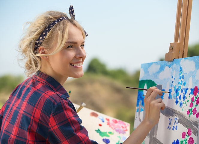 Smiling woman gets creative with art while painting a colorful landscape for emotional well-being