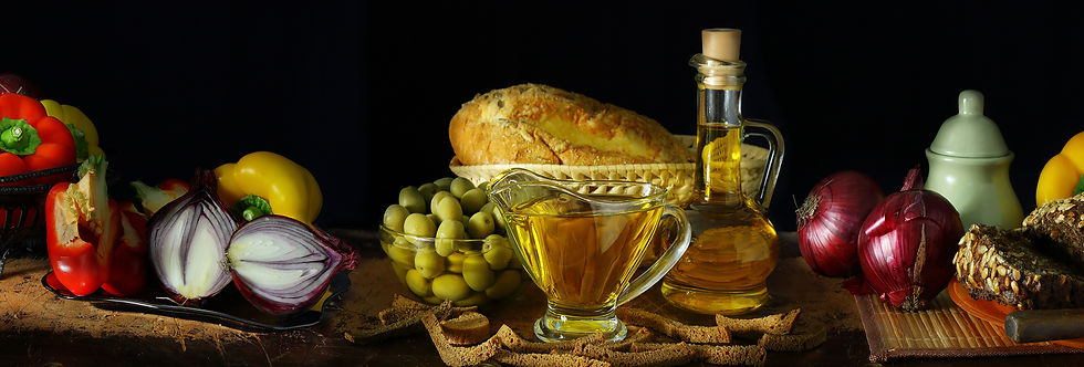 A still life of fresh vegetables, olives, bread, and oil to inspire creativity.