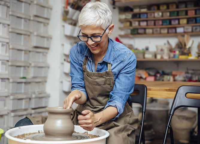 Smiling older woman benefits from a creative adventure as she creates at a pottery wheel for an ageless, healthy brain