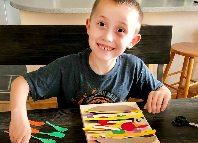Smiling boy inspired to create a Matisse cutouts Dagwood sandwich with premium, colored paper encourages emotional well-being