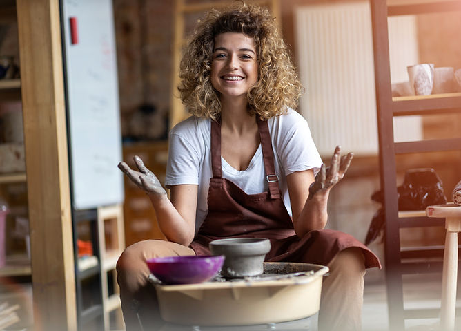 Smiling woman experiencing the benefits of art at pottery wheel with clay on her hands for creative outlet to relieve tension