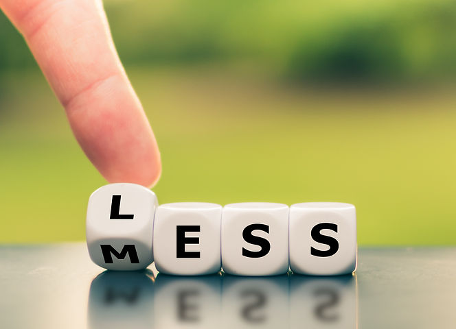 Finger changing a letter on dice to spell the word less with a natural, green background