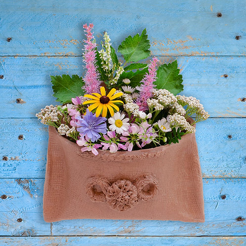 Creative wall flower pocket vase full of dried flowers on blue barn board made with all-natural clay from mini art box kit