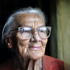 An older woman with wrinkles wearing glasses to inspire creativity