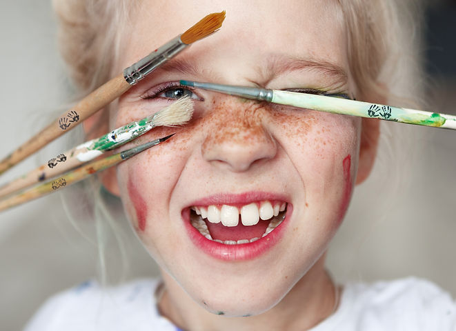 Girl with paint on her face and paint brushes in hands looking excited after sparking creativity with adventure