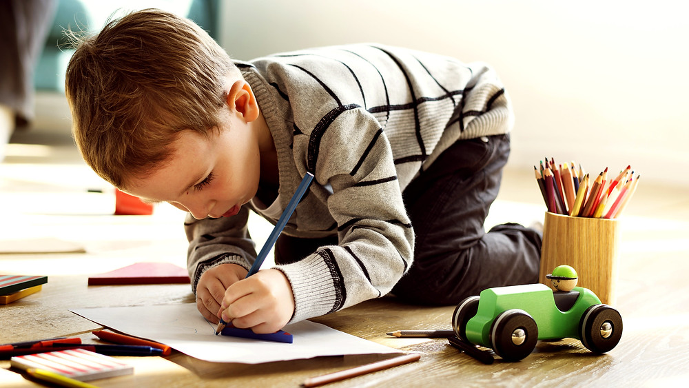 a young boy drawing in a journal with colored pencils