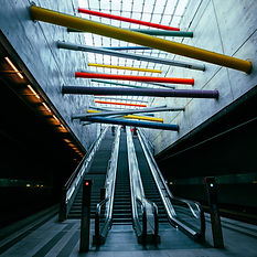 Colorful metal line sculpture above an escalator to inspire creativity