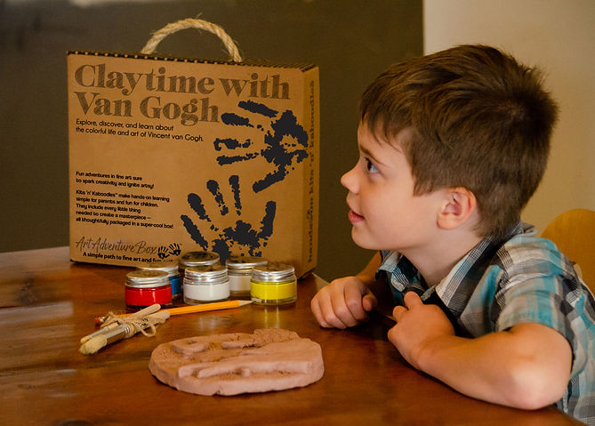 Smiling boy with Claytime with Van Gogh art box ready to paint his terra cotta air dry clay artwork