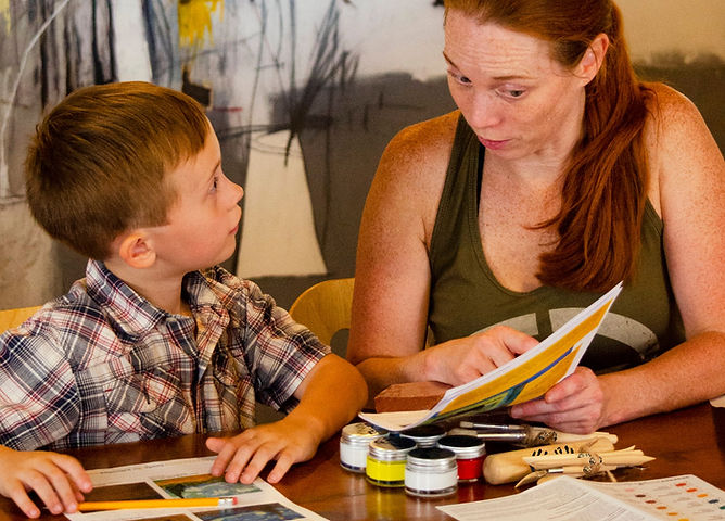 Mom and son looking at Art Kits 'n' Kaboodles full of artsy learning for families with guided instruction and activites, acrylic paints, clay tools