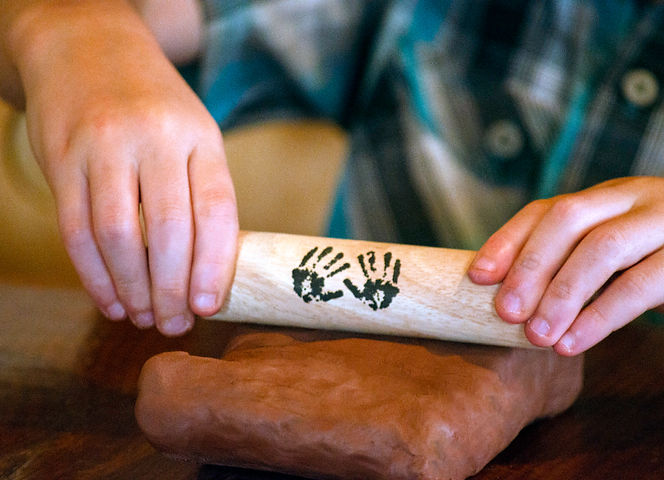 Child's hands rolling all natural, air-dry clay with a sustainable, wood clay tool for Earth-friendly creativity