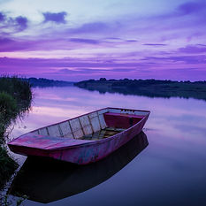 An empty boat on a lake during a purple sunset to inspire creativity