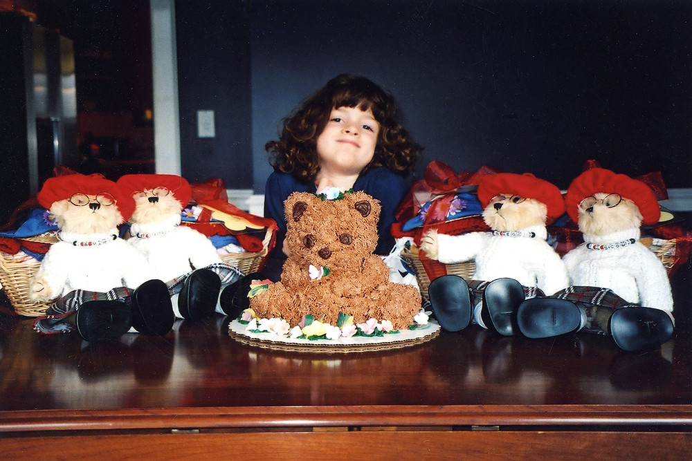 a smiling girl surrounded by teddy bears and a teddy bear cake