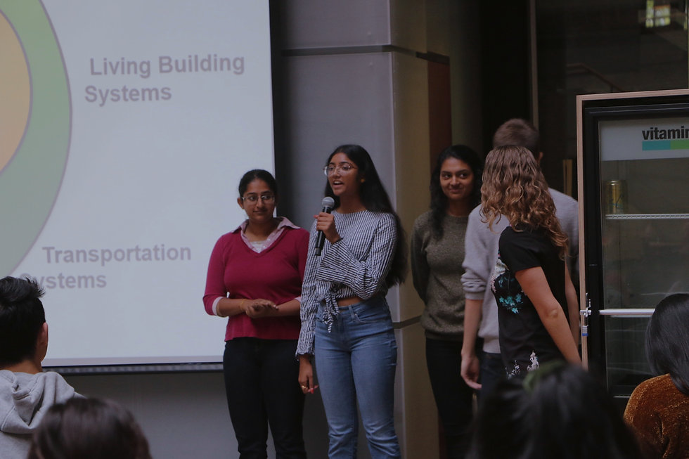 Students giving a presentation in front of a large screen