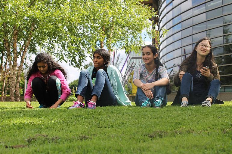 Four children sit in the grass