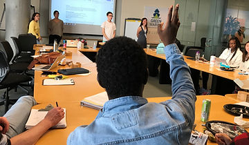 Person raising their hand as students present