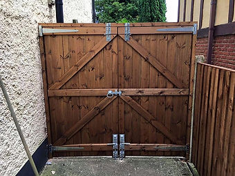 Wooden double gate adjoining house wall