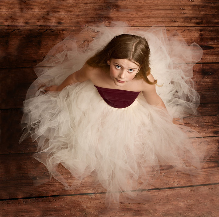 Photograph taken from above of a 10 year old girl in a ivory tule skirt with burgandy top on dark wood floor by children's photographer in North Ferriby