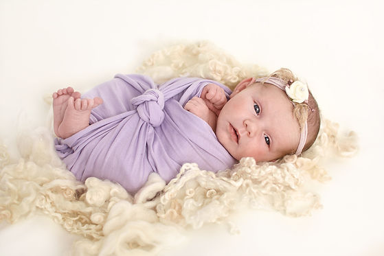 Photograph of baby girl in a lavender wrap and headband on lambs wool