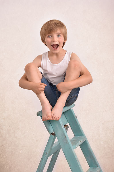 Photograph of 7 year old boy sat a top blue wooden ladders hugging his knees in North Ferriby children's photography session