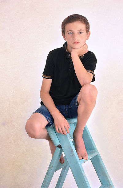 Photograph of 10 year old boy sat a top blue wooden ladders staring at the camera with his chin proped on his hand by easy yorkshire children's photographer