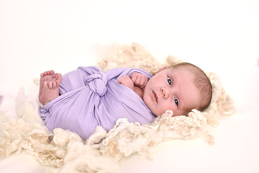 Photograph of awake baby girl layed on cream lambswool in purple wrap by reast Yorkshire newborn photographer
