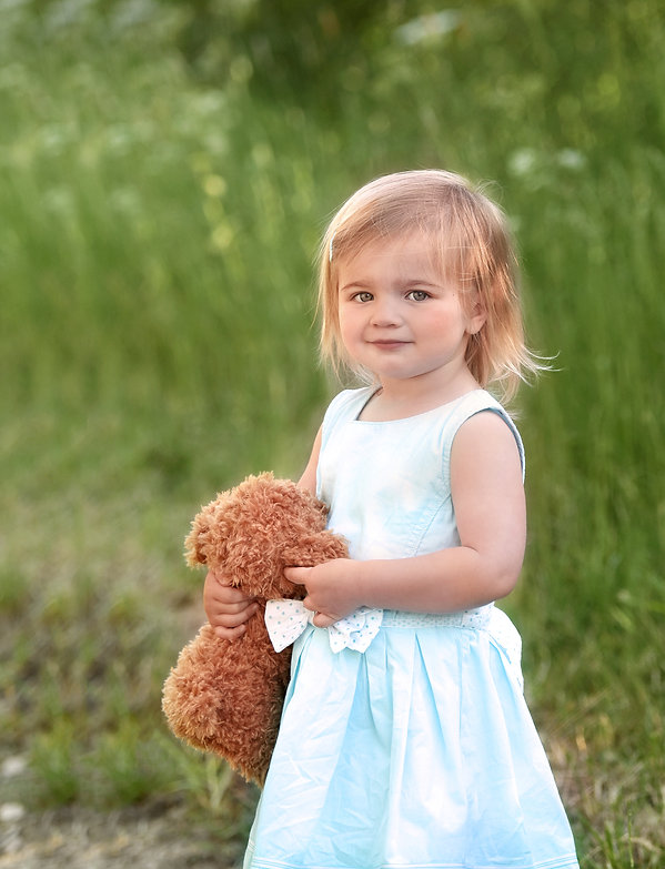 Photograph of 2 year old girl wearing a pale blue summer dress hugging a teddy in North Ferriby parkland by East Yorkshire children's photographer