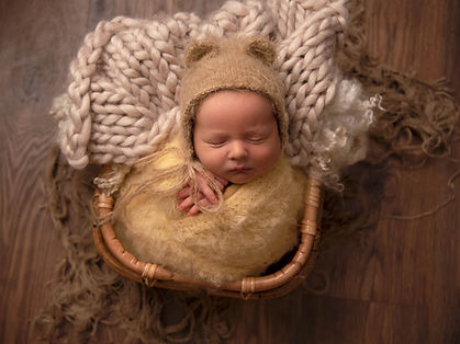 Baby wrapped in yellow woolen wrap, with teddy bonnet sat in bamboo basket with fluffy lay