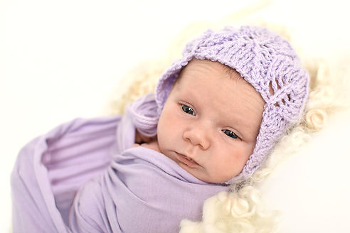 Pphotograph of newborn girl in lavender bonnet and wrap in Hull Newborn photography studio