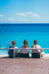 Throuple sitting together on the beach i