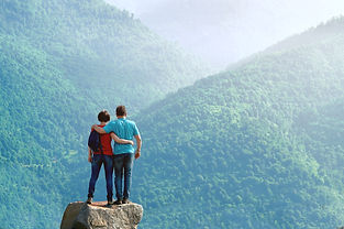 Couple of hikers standing embraced on th