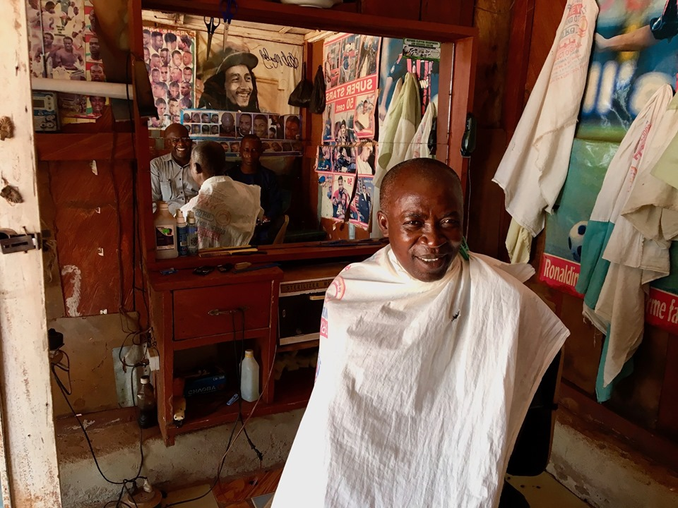 Stephen gets his hair cut in Walewale with Bob Marley looking on in approval.